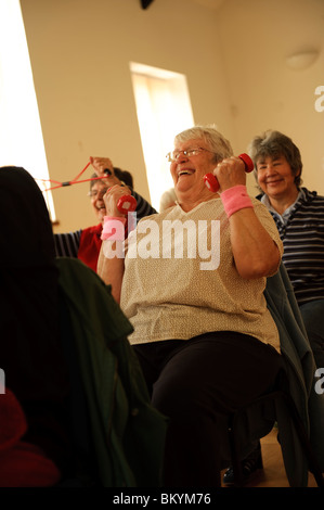 senior citizens participating in a low-impact chair aerobics class in a small village hall in west wales UK - Stock Photo