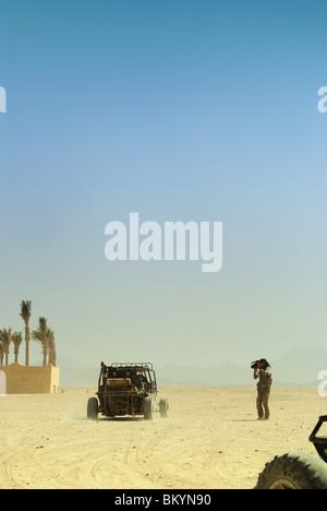 Operator filming desert safari, North Africa, Egypt - Stock Photo