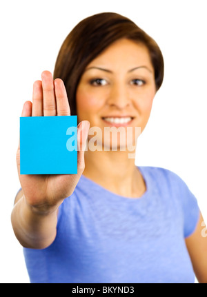 Young woman has a blue sticky note on the palm of her outstretched hand - Stock Photo