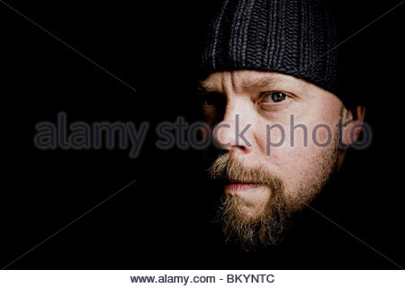 Portrait of professionel flyfisherman Mattias Drugge, Sweden. He is wearing a black hat and has a short beard. - Stock Photo