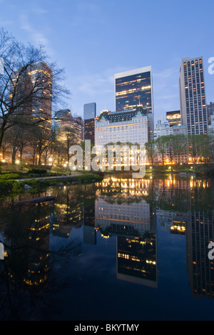 Looking south from Gapstow Bridge across the Pond at the Plaza Hotel at dawn in Central Park. - Stock Photo