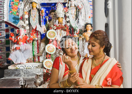 Woman admiring bangles of her daughter-in-law - Stock Photo
