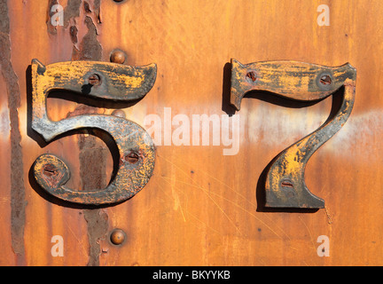grungy rusty number five and seven 57 on old yellow metal train - Stock Photo