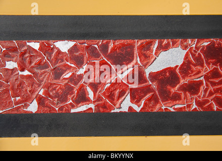 close-up painted side of a train with red pealing paint and black and yellow colors - Stock Photo
