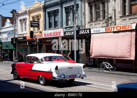 Red and white classic Cadillac on street in the Melbourne suburb of Fitzroy - Stock Photo