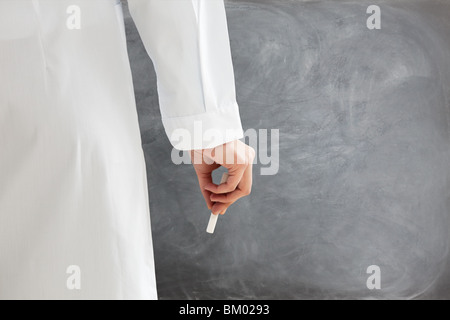 rear view of female teacher in lab clothes holding chalk against blank blackboard. Copy space - Stock Photo