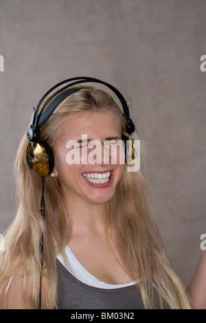 Teen girl smiles wears headphones - Stock Photo