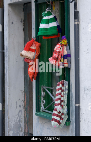 Hand knitted woollen hats and socks for sale outside a private house in Viana do Castelo with green window frame - Stock Photo