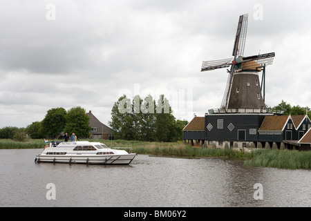 Crown Blue Line Houseboat & Windmill, Geeuw River, Ijlst, Frisian Lake District, Netherlands Stock Photo