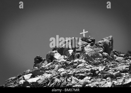 cross sits on top of a sandia mountain boulder mound landscape in black and white, along route 66, albuquerque, - Stock Photo