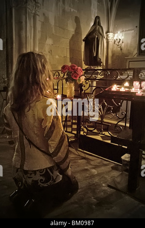 A woman kneels in devotion among lit candles in a church - Stock Photo