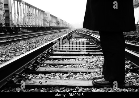 A man wearing dark trousers and coat standing on a railway line - Stock Photo
