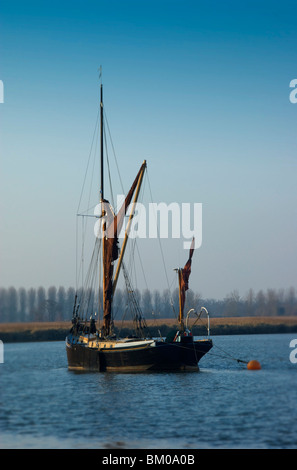 An old sailing boat on a wide river - Stock Photo