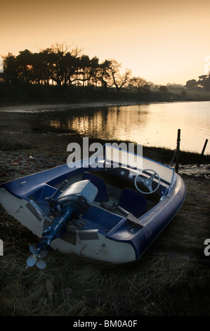 A small power boat on the banks of a river with setting sun behind trees, Suffolk England - Stock Photo