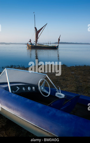 Speed boat on shore with old sail boat on river, Eiken Suffolk England - Stock Photo