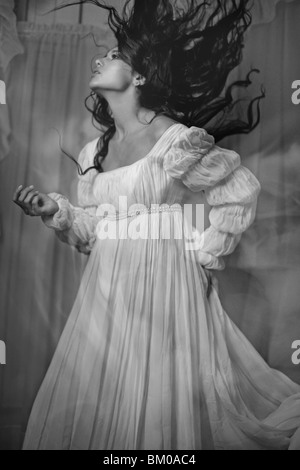 A young woman with long dark hair wearing a white dress - Stock Photo