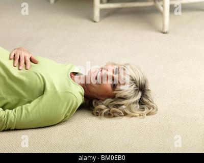 Mature pregnant woman lying on floor - Stock Photo