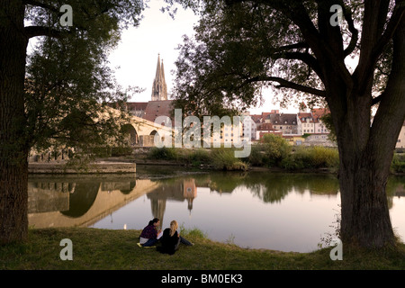 Two young girls sitting on the banks of the river, Stone bridge and Regensburg cathedral, cathedral of St. Peter, - Stock Photo