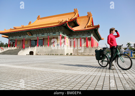 Young German woman on bicycle in front of National Theatre and National Concert Hall, Taipei, Republic of China, - Stock Photo