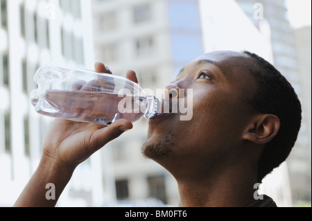 Young man drinking water, Cape Town, Western Cape Province, South Africa - Stock Photo