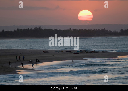 Fishermen pulling in net from shore at sunset, Barra, Inhambane Province, Mozambique - Stock Photo