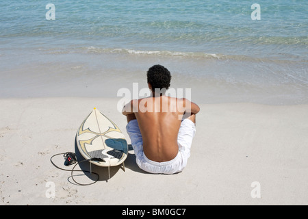 Rear view of young man sitting on beach with surfboard - Stock Photo