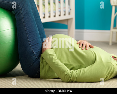 Pregnant woman lying on floor exercising - Stock Photo