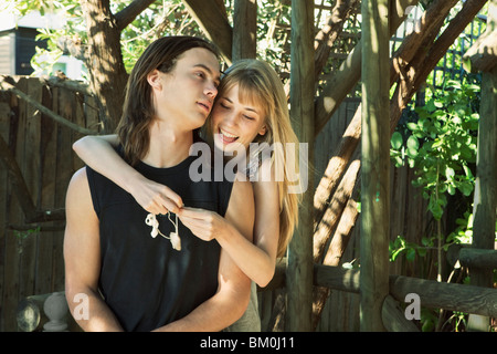 Girl putting shell necklace on young man - Stock Photo