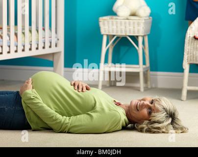 Pregnant older woman lying on floor - Stock Photo