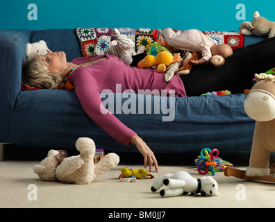 Senior woman asleep on sofa with toys - Stock Photo
