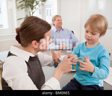 Businesswoman, boy playing string game - Stock Photo