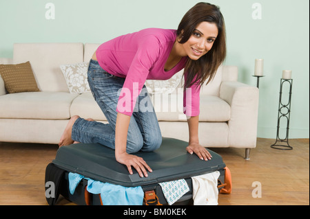 Woman trying to close overfull suitcase - Stock Photo