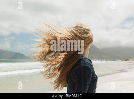 Young womans hair blowing in wind - Stock Photo