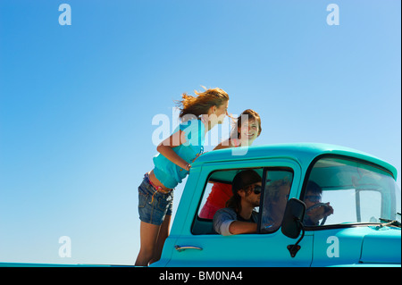 5 young people traveling in pickup truck - Stock Photo