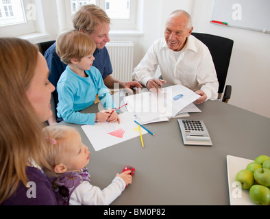 Advisor discussing papers with a family - Stock Photo