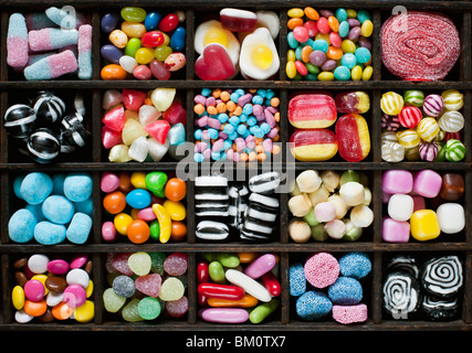 Colourful assorted childrens sweets and candy in a wooden tray - Stock Photo