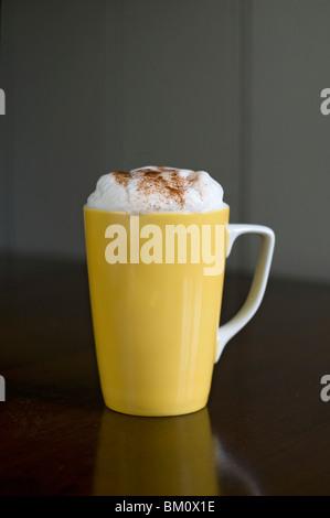 yellow mug of cappuccino, plain background - Stock Photo
