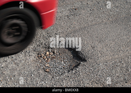 Car passing a pot hole in a suburban road in Hounslow, Middx, UK. May 2010 - Stock Photo