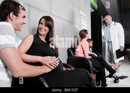 Patients and a doctor in a waiting room - Stock Photo