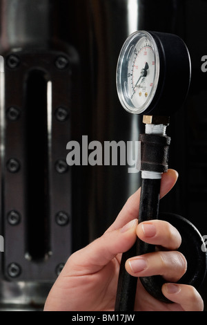 Female doctor holding a pressure gauge in a laboratory - Stock Photo