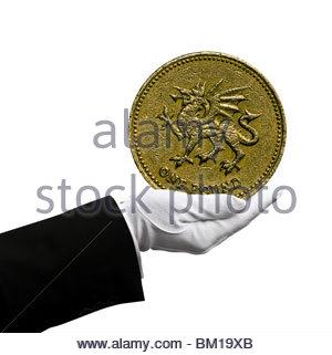 Holding pound coin - Stock Photo