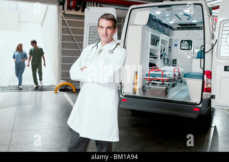 Doctor standing in front of an ambulance - Stock Photo