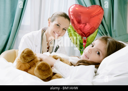 Girl on a hospital bed with a female doctor beside her - Stock Photo