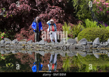 A walk in the Japanese Garden. An elderly couple pause by a reflecting pond in a Japanese Garden in spring.