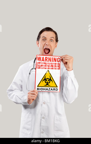Portrait of a doctor showing a Biohazard warning sign - Stock Photo