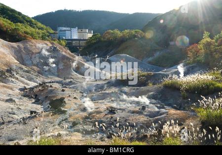 Steam vents in Jigokudani geothermal area, hotels of Noboribetsu Onsen beyond, Shikotsu-Toya National Park, Hokkaido, - Stock Photo