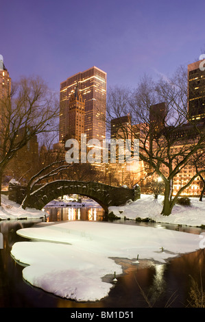 A view of the Gapstow Bridge in Central Park and city skyline at dusk after a snow storm, New York City, New York - Stock Photo
