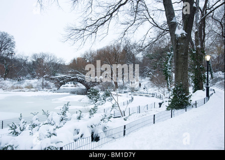 An early morning view of the Gapstow Bridge after a snowfall in Central Park, New York City, New York State, USA - Stock Photo