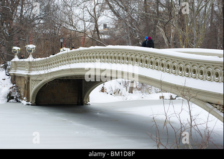 People walking across the Bow Bridge in Central Park after a snowstorm, New York City, New York State, United States - Stock Photo