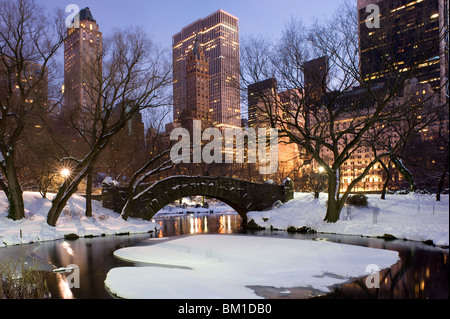 The Gapstow Bridge in Central Park after a snowstorm with skyscrapers behind at dusk, New York City, New York State, - Stock Photo